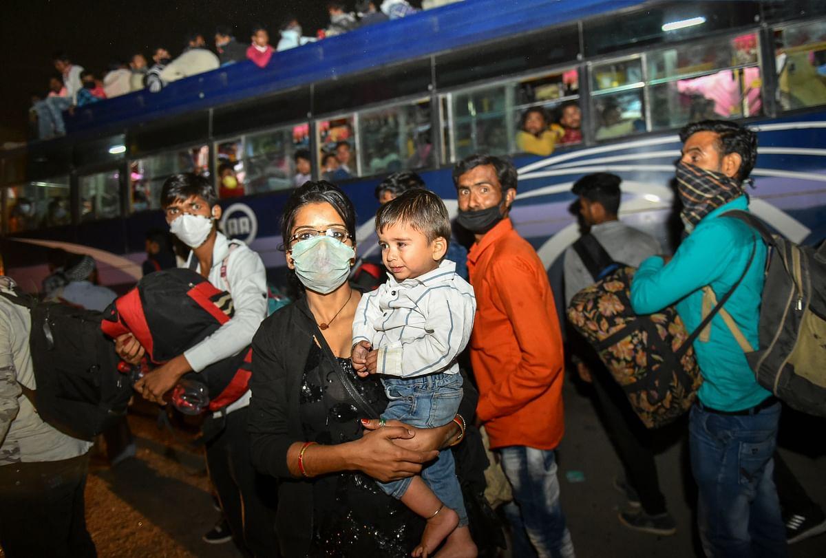 कोरोना के भय के बीच लॉकडाउन के बावजूद अपने घर लौटने की आस लिये दिल्ली की सड़क पर बच्चे के साथ खड़ी महिला और उसके पीछे जमी भीड़.