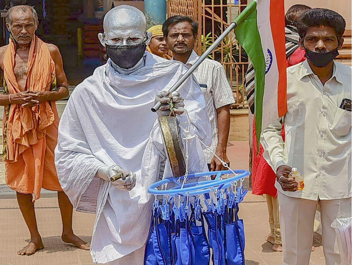 COVID-19 : जब मास्क और सैनिटाइजर बांटने पहुंचे महात्मा गांधी ! तसवीरें वायरल