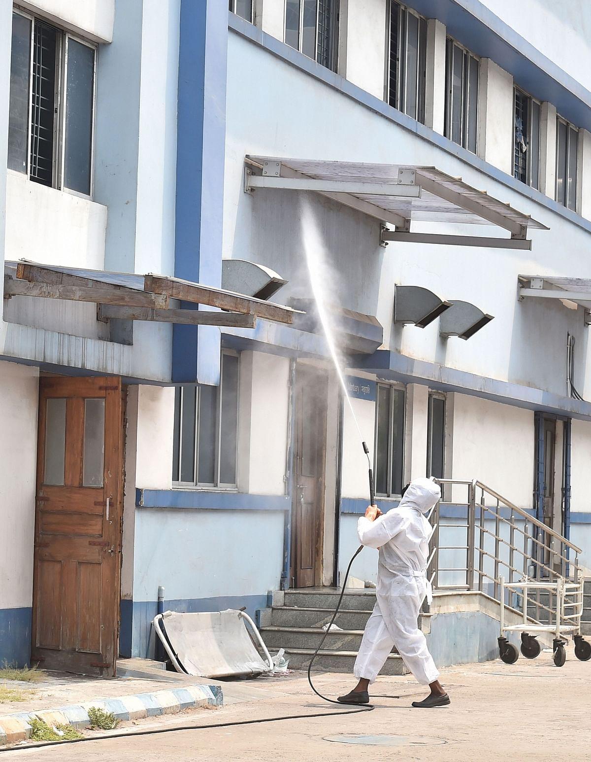 कोलकाता की तसवीर जहां अस्पताल के बाहरी हिस्से को सैनिटाइज करता युवक