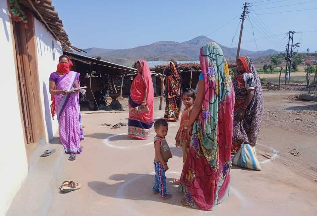 सोशल डिस्टेंसिंग का पालन करते हुए आगनबाड़ी सेविका और सहायिका घर-घर पहुंचा रहीं महिलाओं का पोषाहार