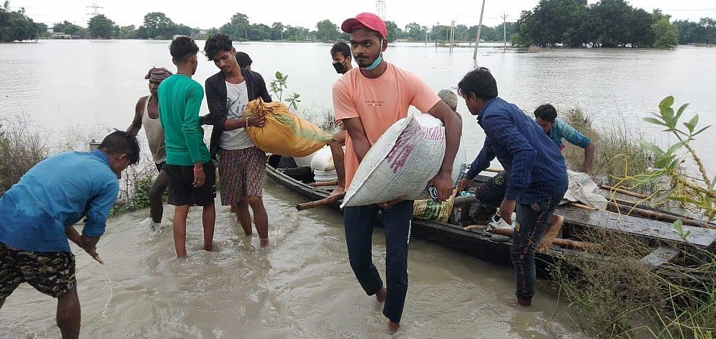 गोपालगंज के प्यारेपुर में नाव से सामान लेकर पलायन करते लोग