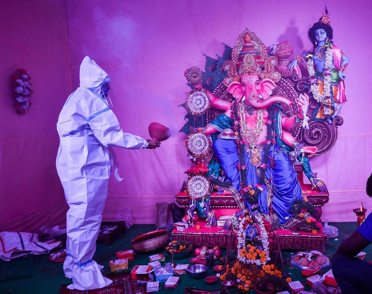 कोरोना संकट के बीच पीपीई किट पहनकर भगवान गणेश की आरती करता भक्त