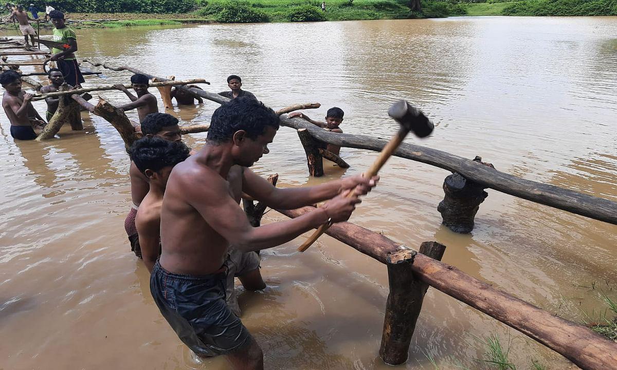 Jharkhand news : तालाब में प्रवेश कर श्रमदान से बांस एवं लकड़ी से पुल बनाते ग्रामीण.