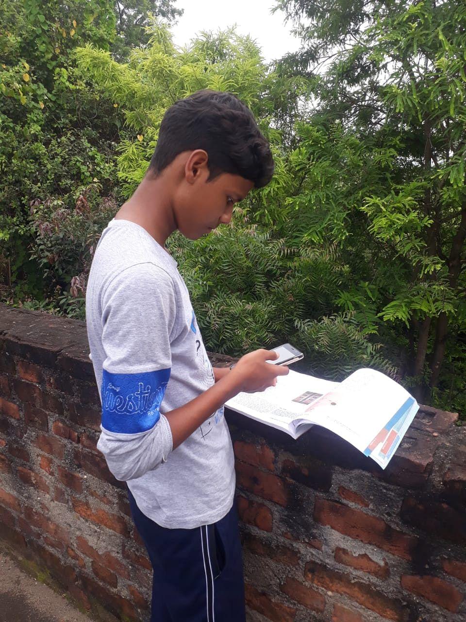 अपने घर की छत पर नेटवर्क ढूंढता छात्र