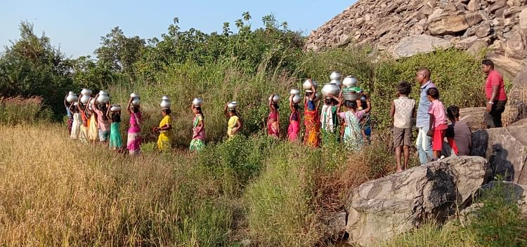 After hours of effort, women get water.  Then all the villages go together.