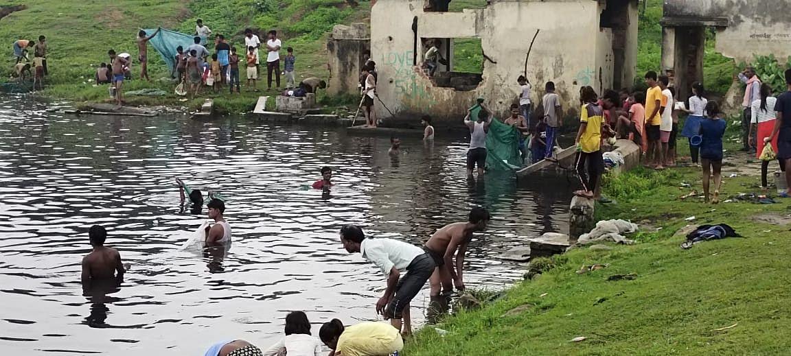 गिरिडीह में तालाब में मछली पकड़ रहे ग्रामीण