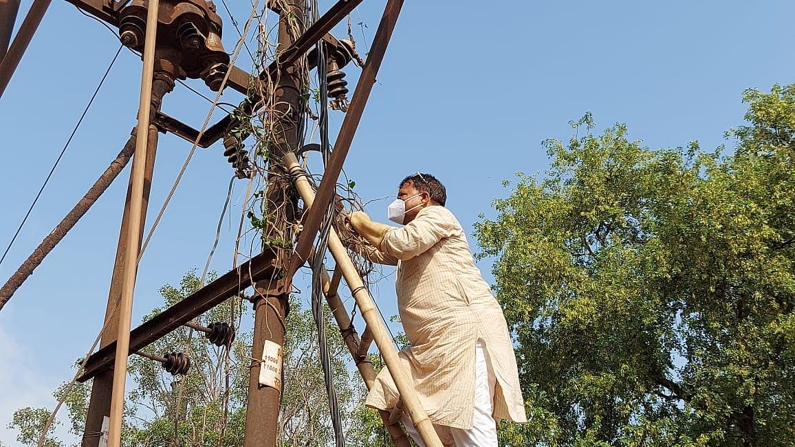 जानें, हाथ में हंसिया पकड़कर क्यों बिजली के खंभे पर चढ़ गये मंत्री जी...