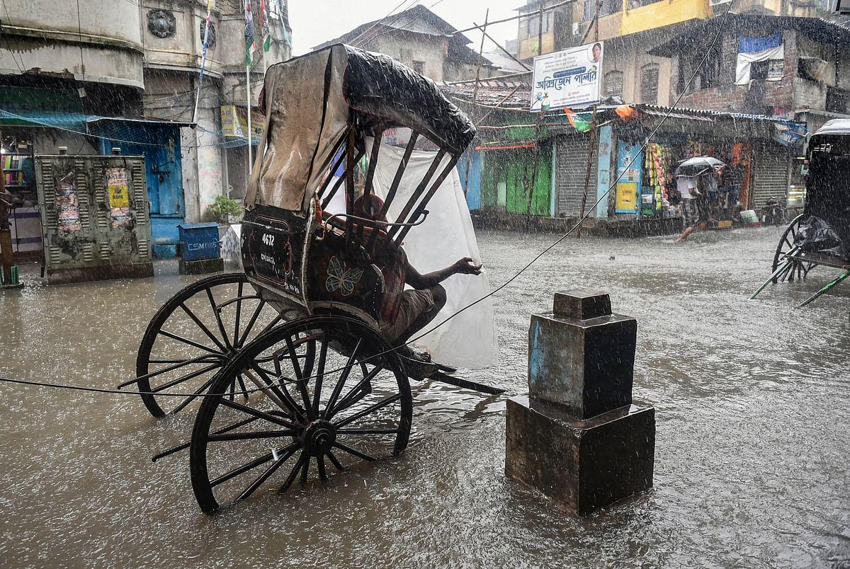 कोलकाता में बीच सड़क पर रिक्शा खड़ी कर बारिश से बचने की कोशिश में रिक्शा चालक