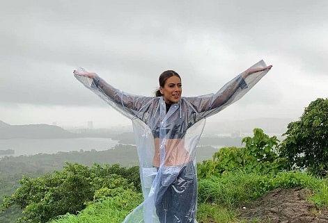 Nia Sharma latest photoshoot in rain wearing a transparent raincoat