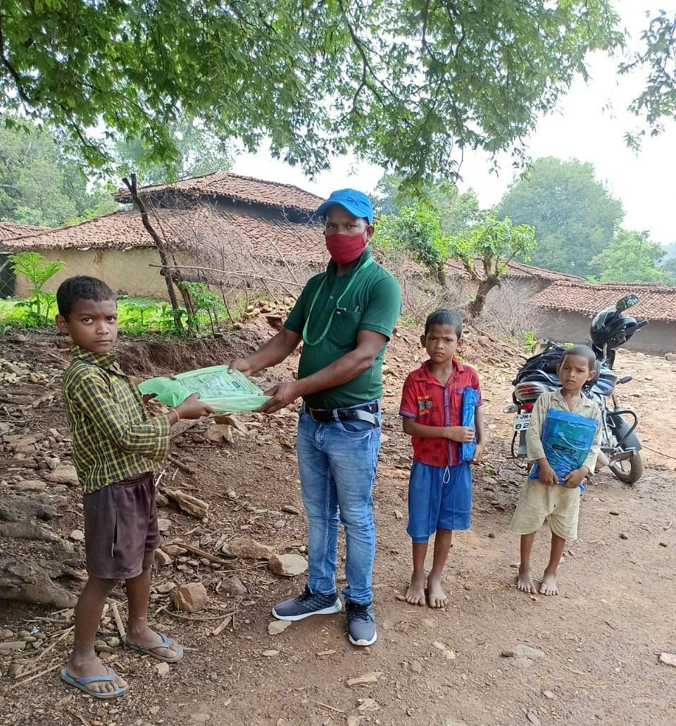 बच्चों को स्कूल सामग्री देते टीचर हेमंत कुमार सिंह