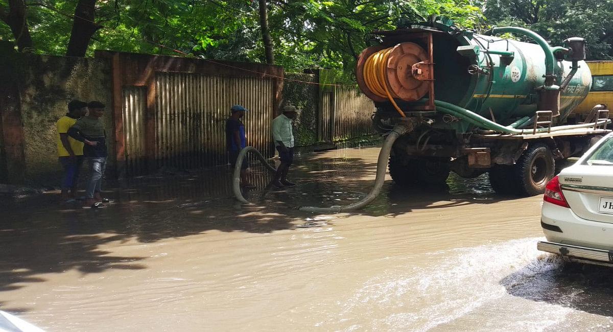 लगातार बारिश के कारण रांची के सड़कों पर जमे पानी को निकालते नगर निगम के कर्मी.