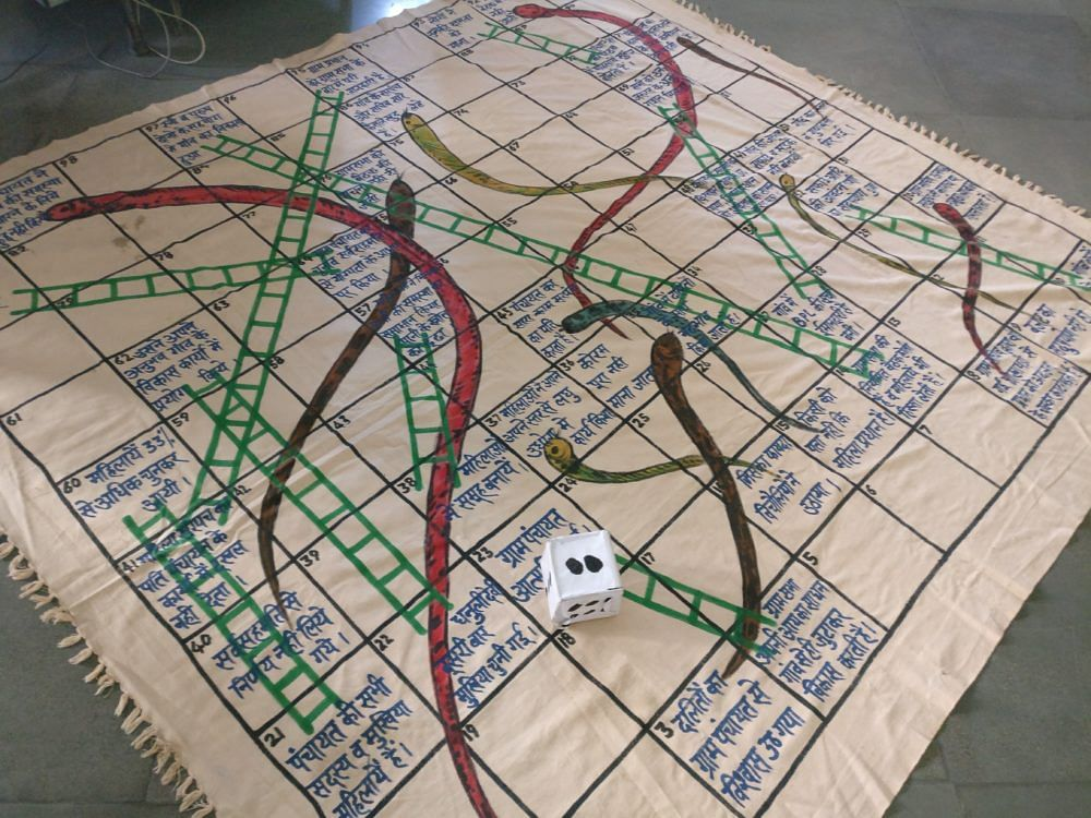 The Snakes and Ladders game used to teach the women