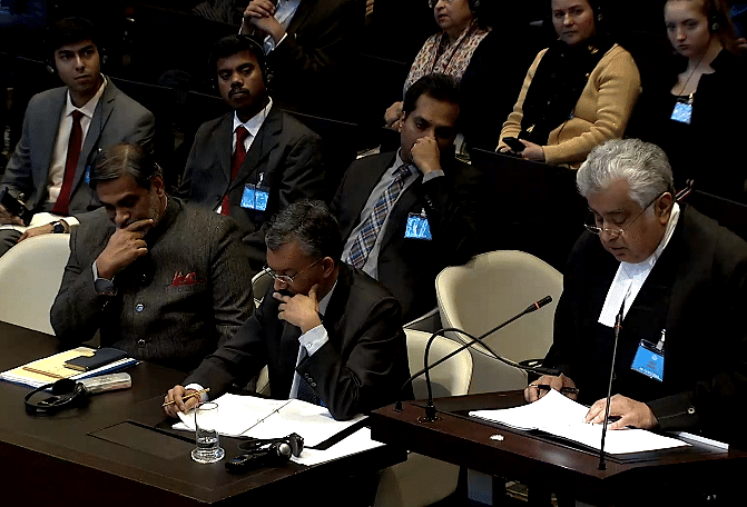 Indian ambassador to the Netherlands, Venu Rajamony (L) and senior Indian diplomat, Deepak Mittal (R) in the backdrop while Harish Salve makes arguments for India