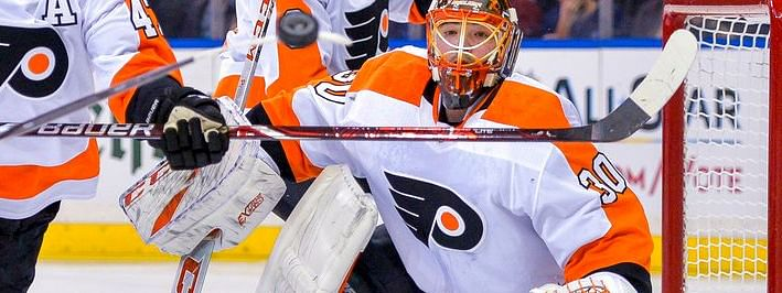 Philadelphia Flyers goaltender Michal Neuvirth (30) keeps his eyes on a flying puck during the second period of an NHL hockey game against the New York Rangers, Sunday, Dec. 23, 2018, in New York. (AP Photo/Howard Simmons)