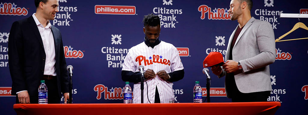 Philadelphia Phillies new outfielder Andrew McCutchen, center, accompanied by general manager Matt Klentak, left, and manager Gabe Kapler, puts on his uniform during a news conference in Philadelphia, Tuesday, Dec. 18, 2018. McCutchen and the Philadelphia Phillies finalized a back-loaded $50 million, three-year contract, a deal that includes a team option for 2022. (AP Photo/Matt Rourke)