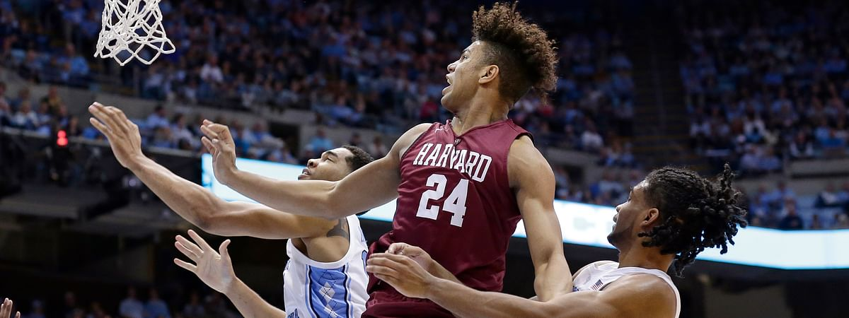 In this January 2019 file photo, North Carolina's Garrison Brooks, left, and Coby White defend against Harvard's Kale Catchings (24) during the second half of an NCAA college basketball game in Chapel Hill, N.C.