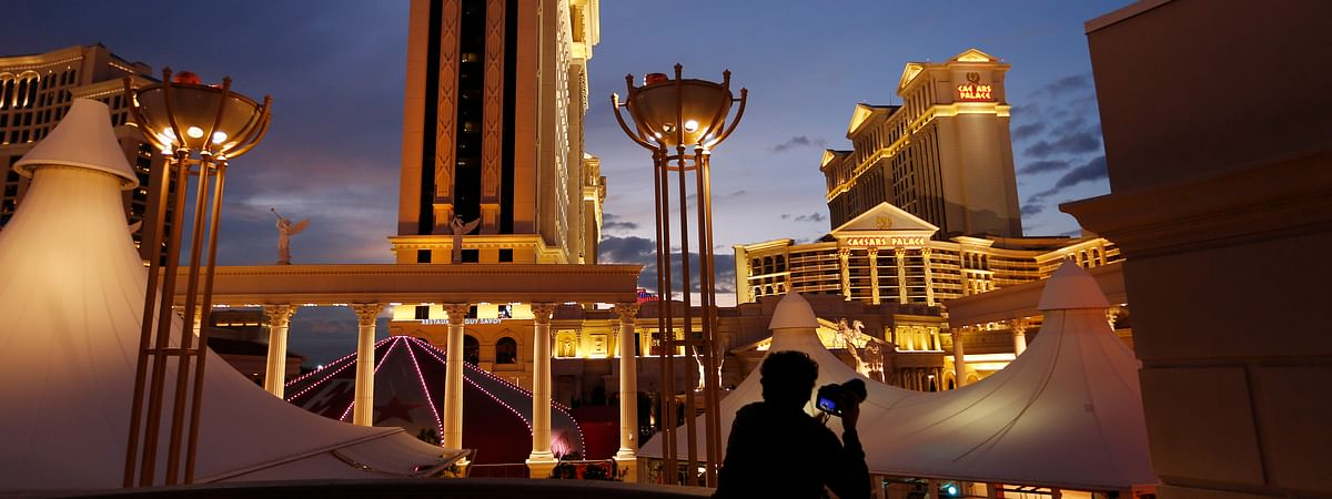 FILE - In this Monday, Jan. 12, 2015, file photo, a man takes pictures of Caesars Palace hotel and casino, in Las Vegas. The NFL is partnering with Caesars Entertainment as its first official casino sponsor, but the deal does not include sports betting or fantasy football. The multiyear arrangement announced Thursday, Jan. 3, 2019, begins with this weekend's playoffs. (AP Photo/John Locher, File)