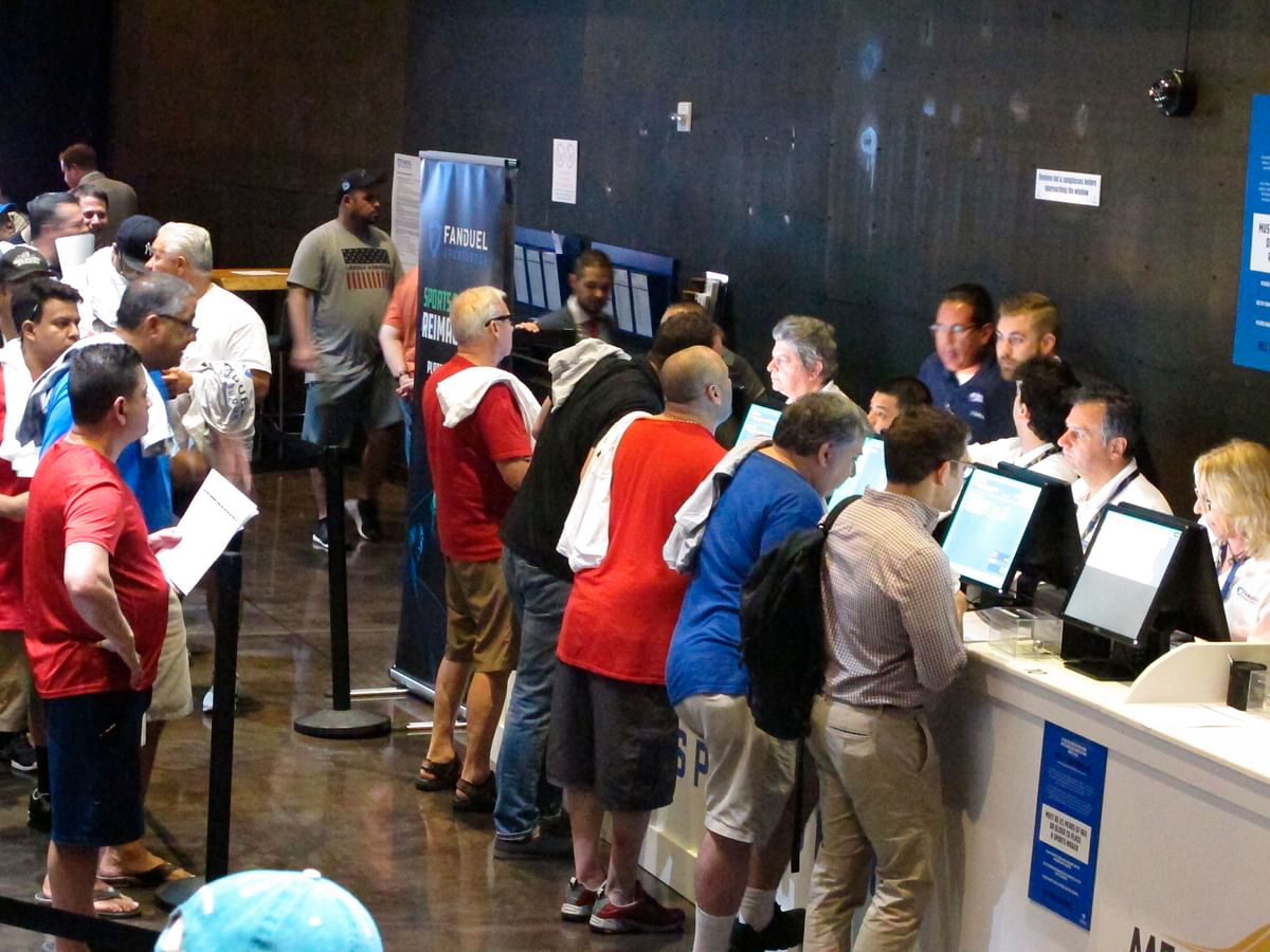 FILE - This July 14, 2018 file photo shows gamblers placing bets on sports events at the FanDuel sports book at the Meadowlands Racetrack in East Rutherford, N.J., on the day it opened. The race to legalize sports betting is on now that the U.S. Supreme Court has allowed it in all 50 states, but will it provide enough extra tax revenue to make much of a difference for schools, roads or pension debt? (AP Photo/Wayne Parry, File)