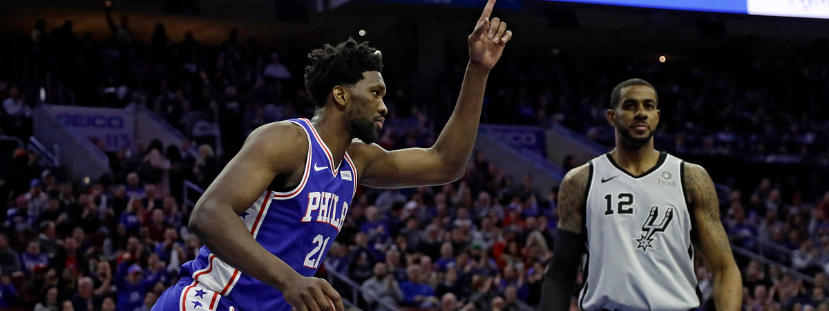 Philadelphia 76ers' Joel Embiid, left, celebrates after a dunk past San Antonio Spurs' LaMarcus Aldridge during the first half of an NBA basketball game, Wednesday, Jan. 23, 2019, in Philadelphia. (AP Photo/Matt Slocum)