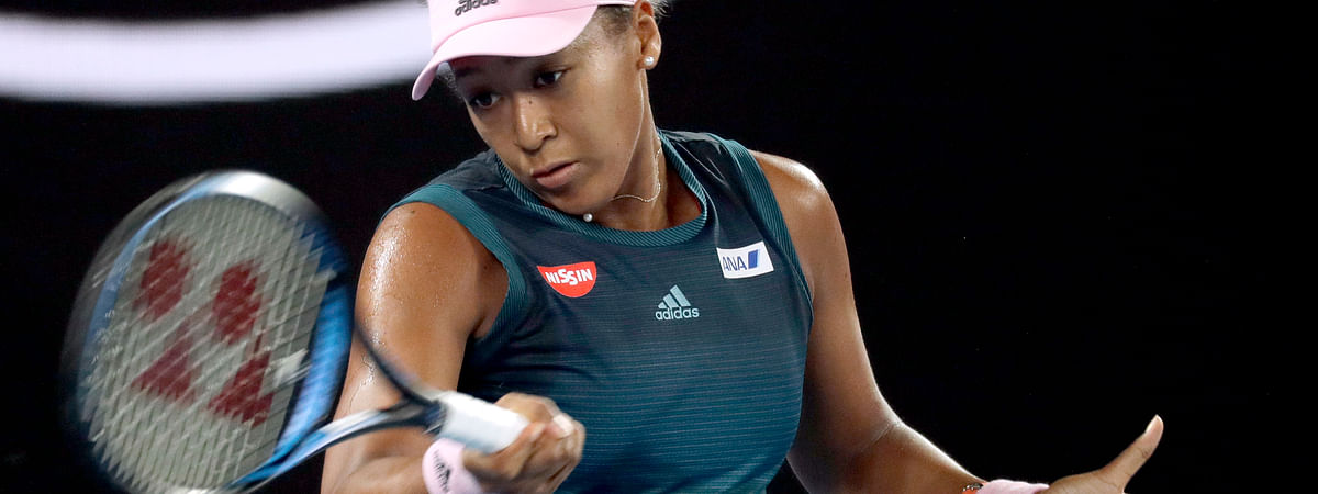 Japan's Naomi Osaka makes a forehand return to Poland's Magda Linette during their first round match at the Australian Open tennis championships in Melbourne, Australia, Tuesday, Jan. 15, 2019. (AP Photo/Kin Cheung)