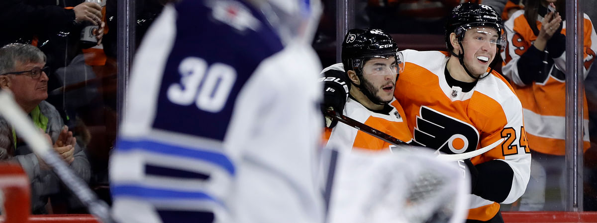 Philadelphia Flyers' Phil Varone, center, celebrates with Mikhail Vorobyev, right, after scoring a goal past Winnipeg Jets' Laurent Brossoit during the second period of an NHL hockey game, Monday, Jan. 28, 2019, in Philadelphia. (AP Photo/Matt Slocum)
