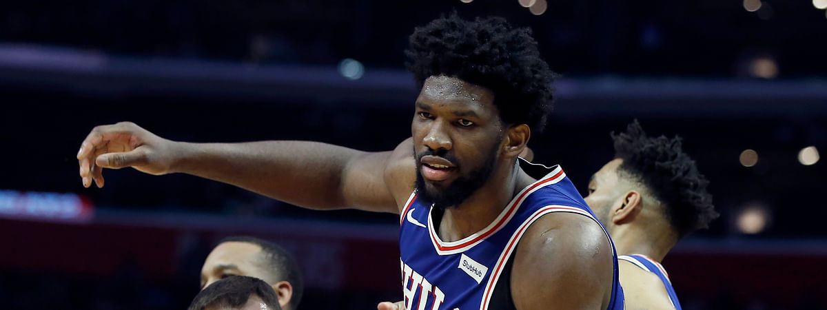 Referee Josh Tiven, left, holds back Philadelphia 76ers center Joel Embiid, center, from an altercation against the Los Angeles Clippers during the second half of an NBA basketball game in Los Angeles, Tuesday, Jan. 1, 2019. (AP Photo/Alex Gallardo)