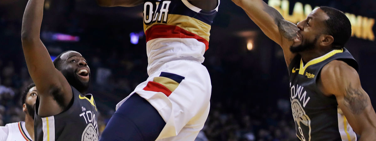 New Orleans Pelicans' Jrue Holiday, center, is fouled by Golden State Warriors' Andre Iguodala, right, during the first half of an NBA basketball game Wednesday, Jan. 16, 2019, in Oakland, Calif. (AP Photo/Ben Margot)