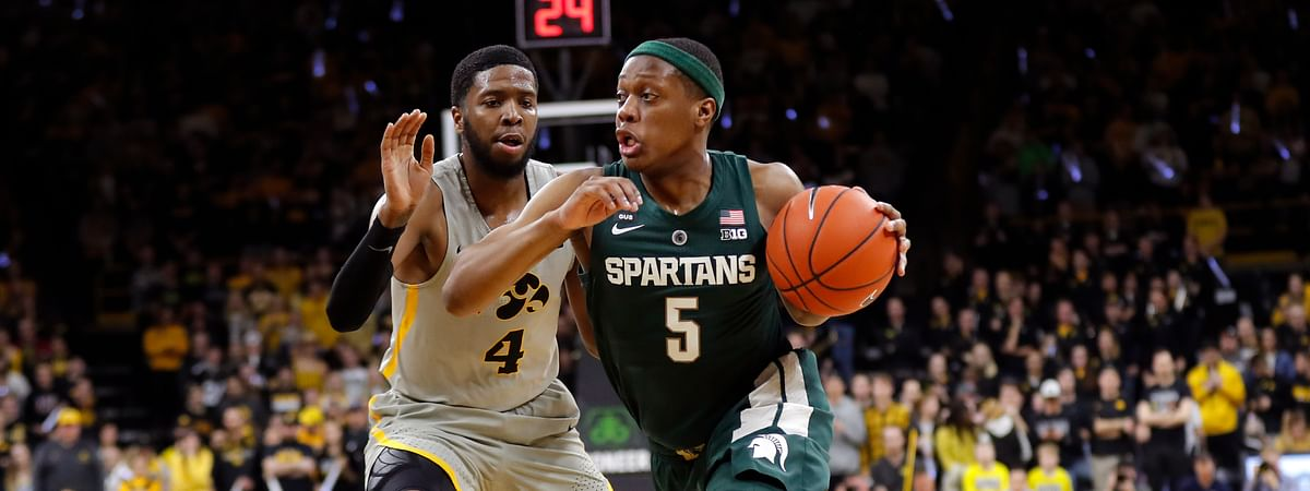 In this January 2019 file photo, Michigan State guard Cassius Winston (5) drives past Iowa guard Isaiah Moss (4) during an NCAA college basketball game in Iowa City, Iowa.
