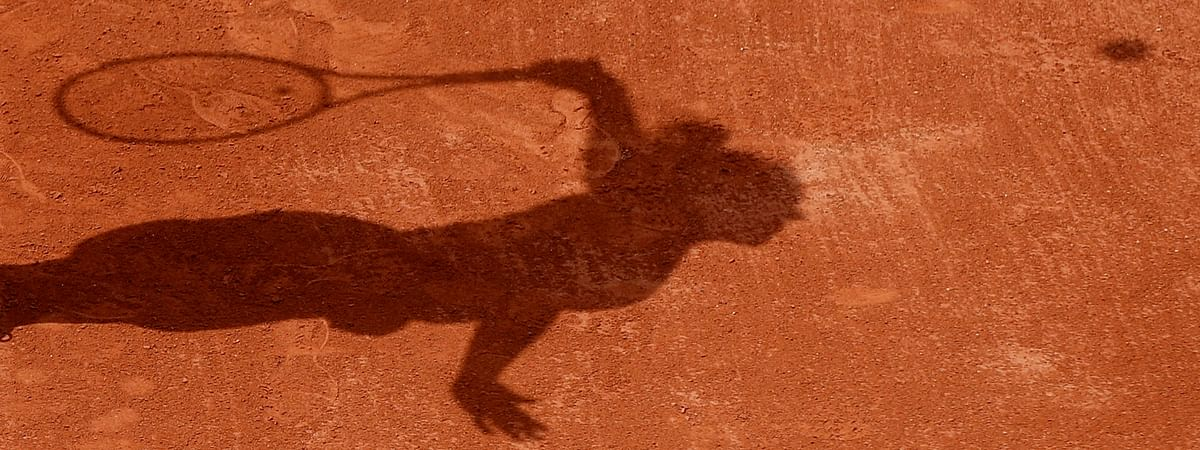 FILE - In this Tuesday, May 30, 2017 file photo a tennis player casts a shadow on the clay as they serve during a tennis match at the French Open tennis tournament at the Roland Garros stadium in Paris. Four people are in French custody on suspicion of fixing matches for an Armenian based in Belgium believed behind an illegal gambling syndicate suspected of fixing hundreds of matches. (AP Photo/Petr David Josek, File)