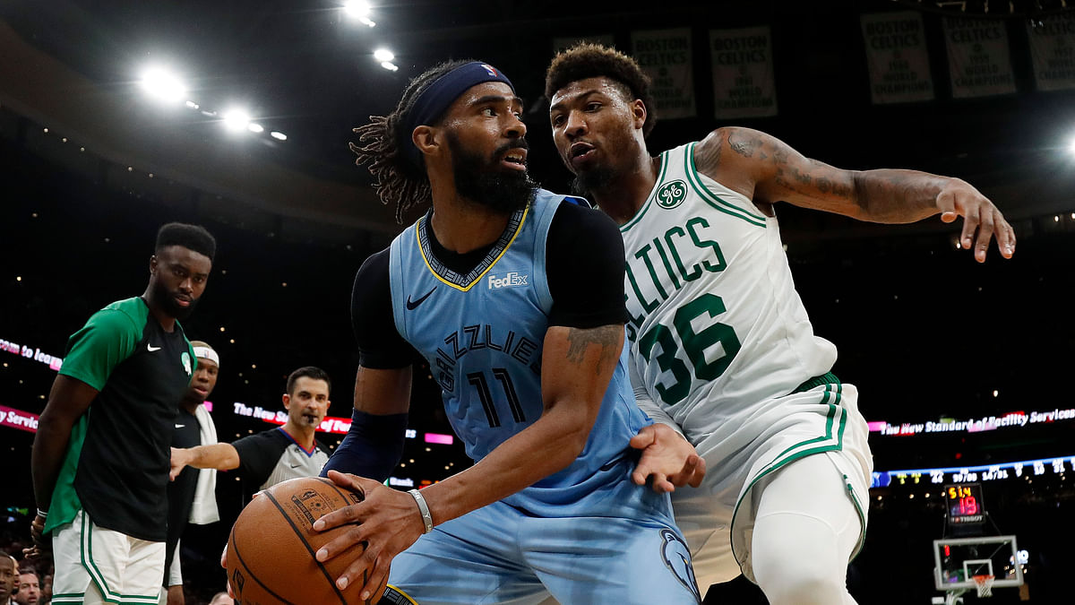 Memphis Grizzlies' Mike Conley (11) looks for a way around Boston Celtics' Marcus Smart, before Smart got injured.