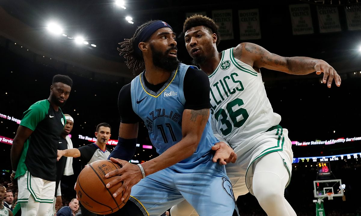 Memphis Grizzlies' Mike Conley (11) looks for a way around Boston Celtics' Marcus Smart.