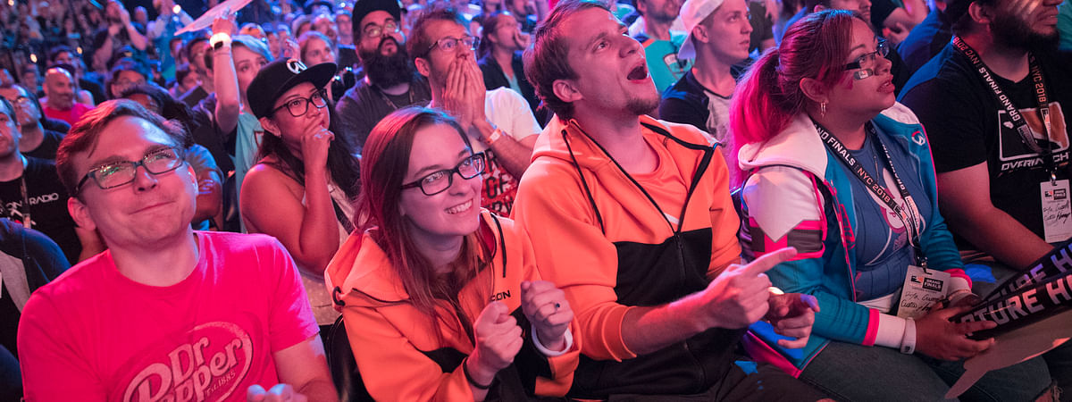 FILE - In this July 28, 2018 file photo, Philadelphia Fusion fans react as the London Spitfire takes the lead during the Overwatch League Grand Finals competition at Barclays Center in the Brooklyn borough of New York. Most professional esports are devoid of female players at their highest levels, even though 45 percent of U.S. gamers are women or girls. Executives for titles like League of Legends and Overwatch say they are eager to add women to pro rosters, but many female gamers say they're discouraged from chasing such careers by toxic behavior and other barriers. (AP Photo/Mary Altaffer, File)