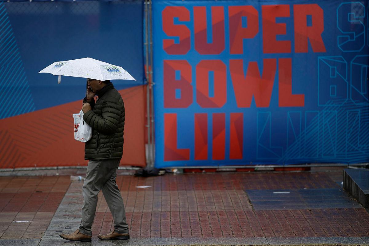 A person walks through Centennial Olympic Park on a rainy morning ahead of the NFL Super Bowl 53 football game, Tuesday, Jan. 29, 2019, in Atlanta. The New England Patriots face the Los Angeles Rams Sunday, Feb., 2, 2019. (AP Photo/Matt Rourke)