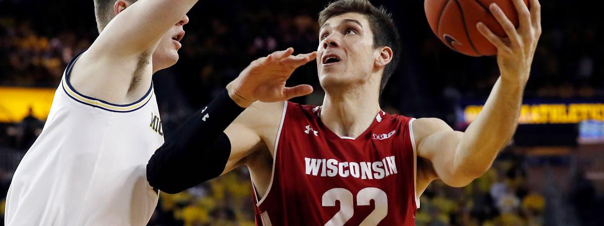 Wisconsin forward Ethan Happ (22) looks to shoot as Michigan center Jon Teske defends Saturday, Feb. 9, 2019, in Ann Arbor, Mich. (AP Photo/Carlos Osorio)