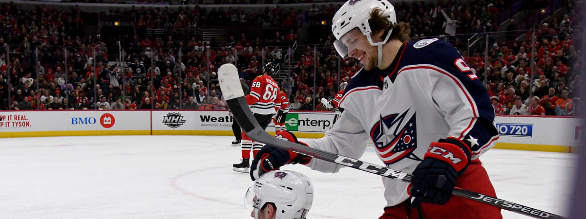 Columbus Blue Jackets center Pierre-Luc Dubois gets a pat on the head from left wing Artemi Panarin after he fell to the ice following a goal against the Chicago Blackhawks. (Matt Marton)