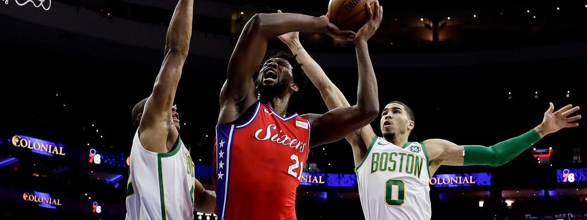 Philadelphia 76ers' Joel Embiid goes up for a shot between Boston Celtics' Al Horford, left, and Jayson Tatum. (AP Photo/Matt Slocum)