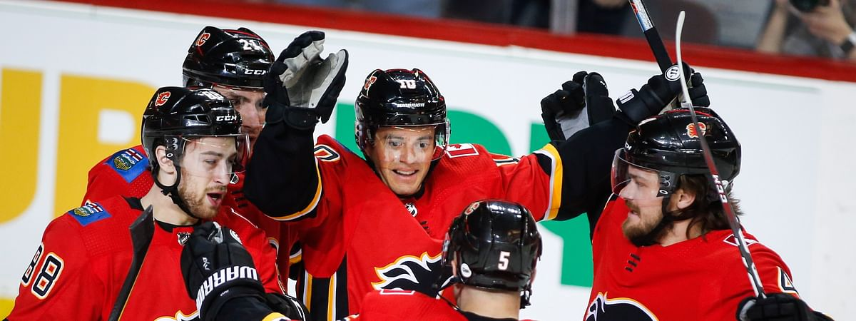 A flicker of Flames celebrate goal by Derek Ryan (center) Monday against the Coyotes
