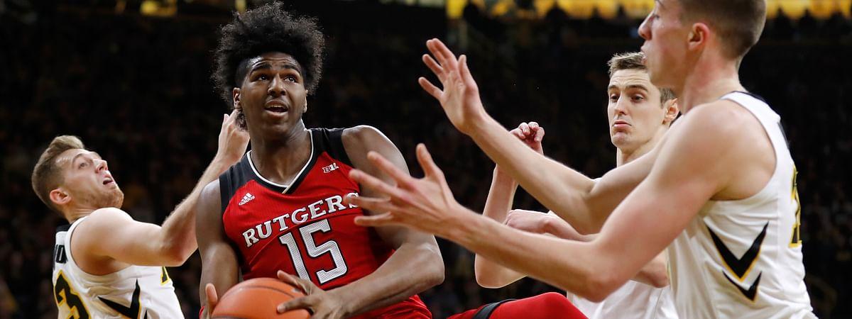 Rutgers center Myles Johnson grabs a rebound between Iowa's Jordan Bohannon, left, Nicholas Baer and Joe Wieskamp, right, during an NCAA college basketball game, March 2, 2019. (Charlie Neibergall)
