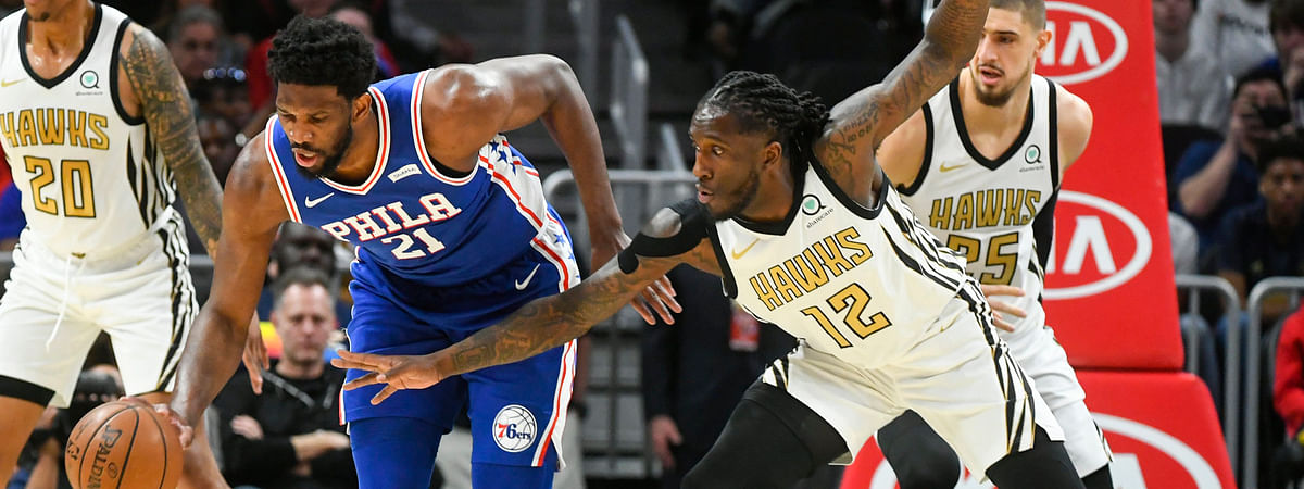 Philadelphia center Joel Embiid  tries to fend off the defense of Hawks forward Taurean Prince  Saturday (John Amis)