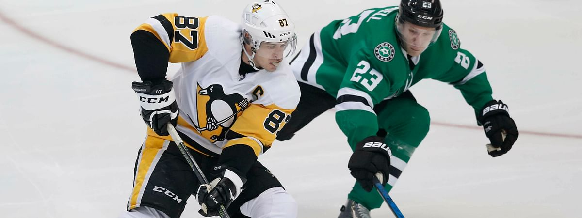 Pittsburgh Penguins center Sidney Crosby and Dallas Stars defenseman Esa Lindell skate for the puck during the game on March 23, 2019.