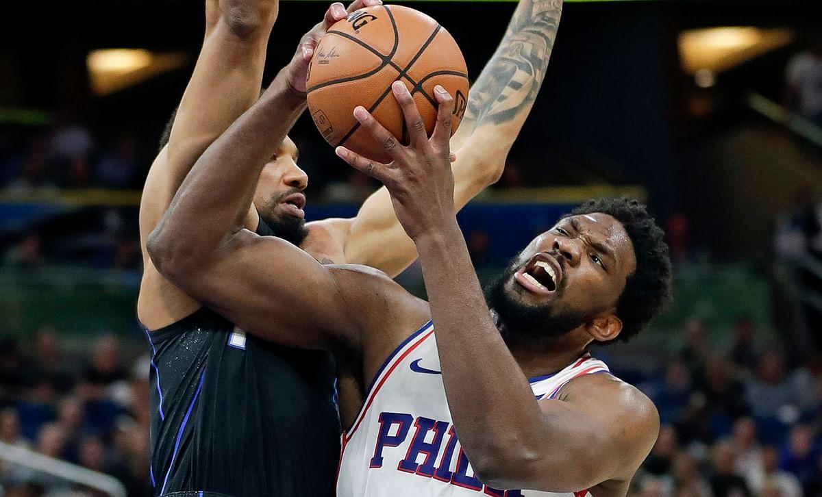 Philadelphia's  Embiid struggles to get his shot up against  Orlando's Khem Birch  Monday (John Raoux)