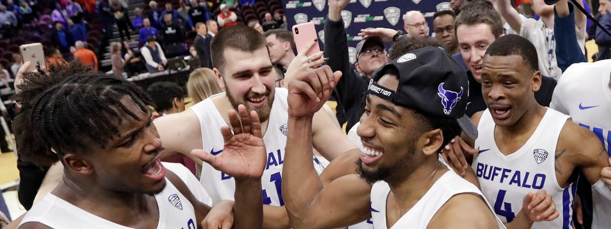 Buffalo's CJ Massinburg and  Nick Perkins (left) and teammates celebrate  NCAA bird Saturday (Tony Dejak)