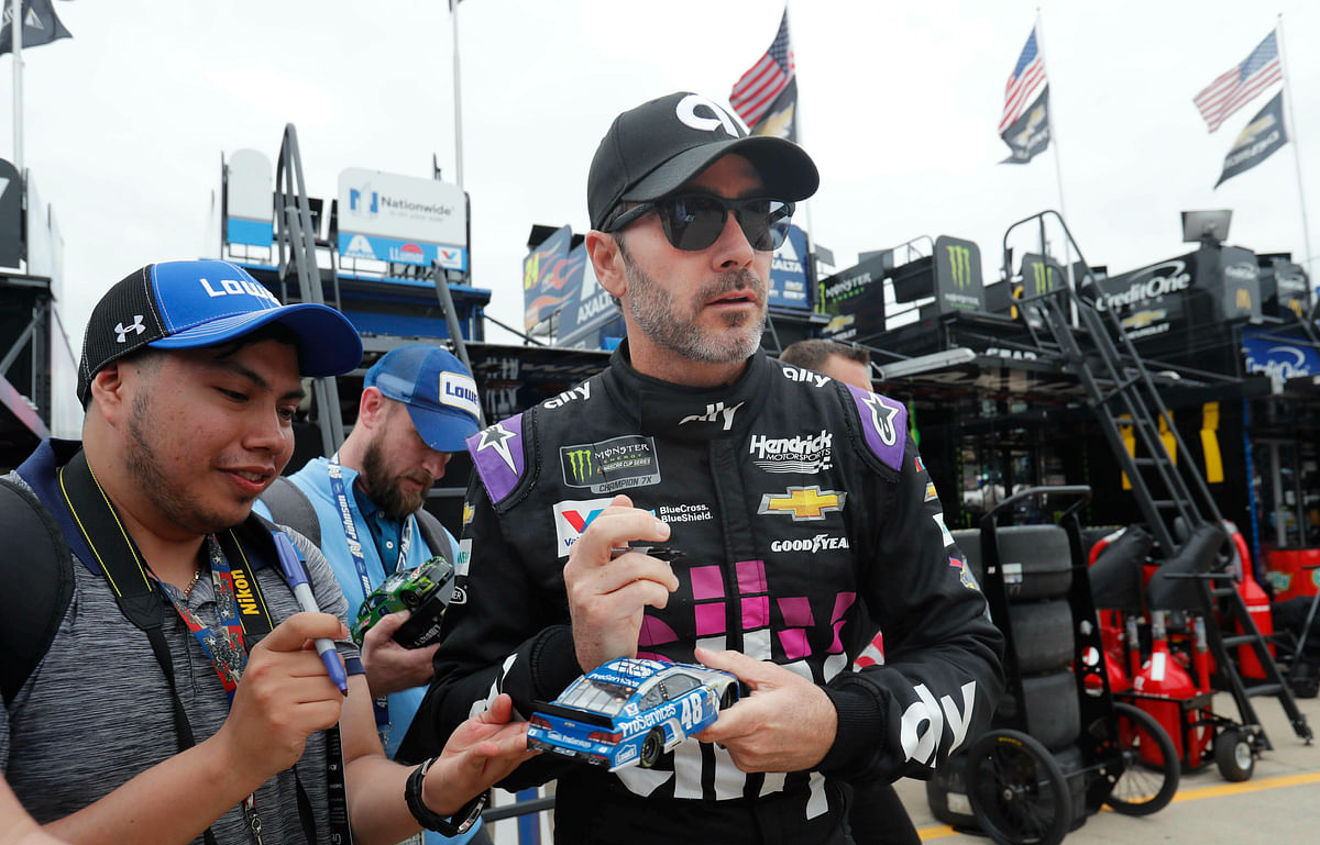 Jimmie Johnson looks up while signing autographs before practice at Texas Motor Speedway in Fort Worth, Texas, Friday, March 29, 2019. (AP Photo/LM Otero)