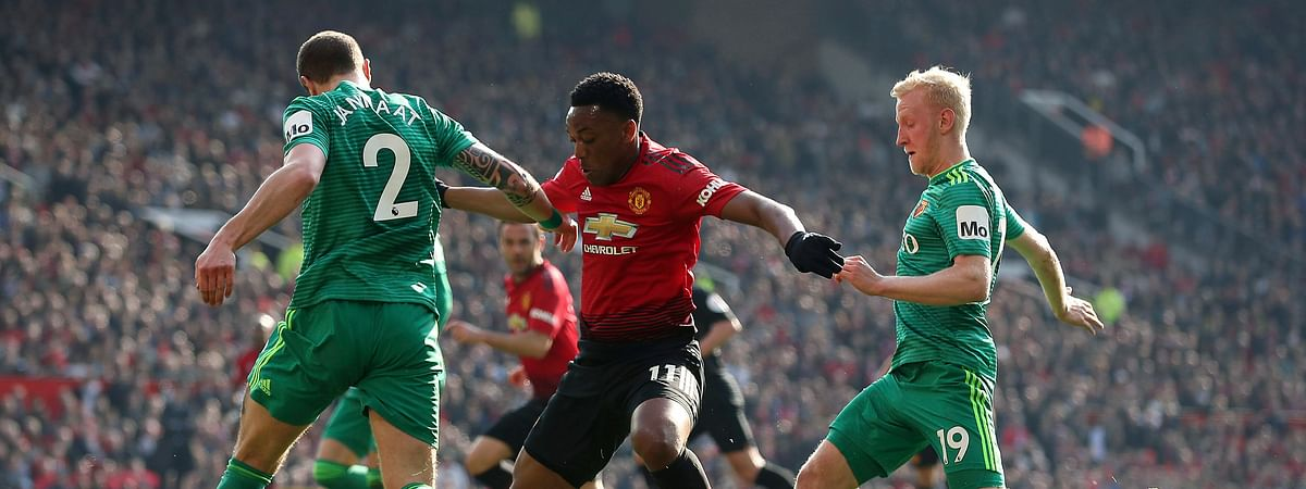 Watford's Daryl Janmaat, left, and teammate Will Hughes, right, battle for the ball with Manchester United's Anthony Martial, during the English Premier League soccer match between Manchester United and Watford on March 30, 2019.