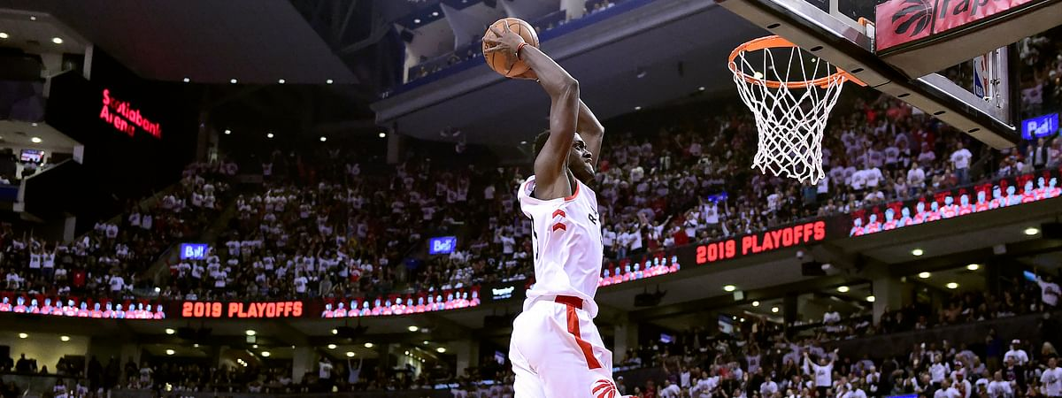 Toronto Raptors forward Pascal Siakam dunks the ball as Philadelphia 76ers forward Tobias Harris tries to catch up during Game 1 of a second round NBA basketball playoff series on April 27, 2019.