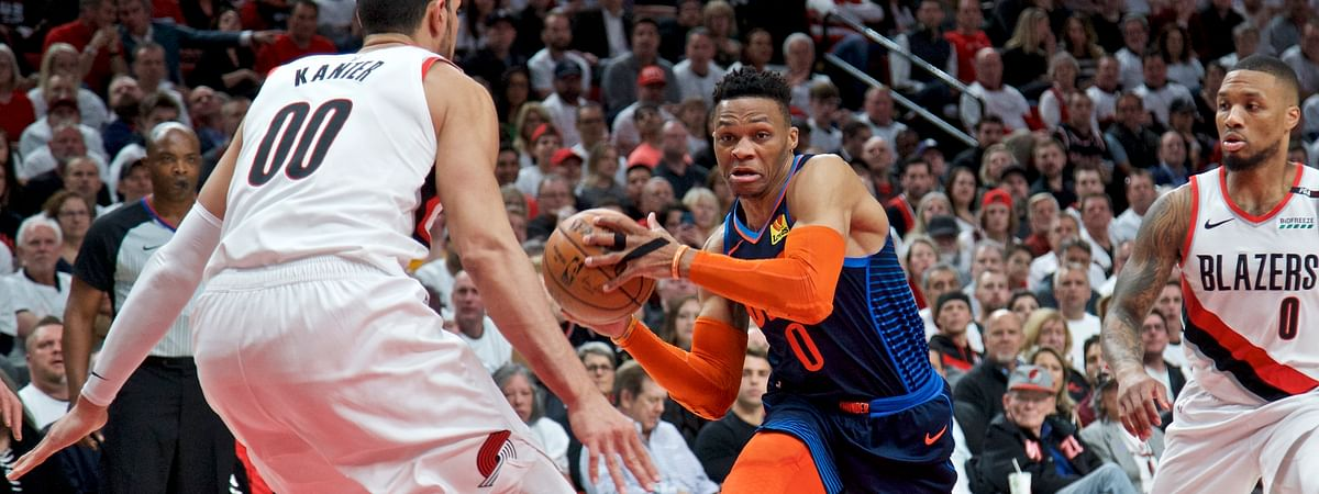 Oklahoma City Thunder guard Russell Westbrook, center, drives to the basket past Portland Trail Blazers guard Damian Lillard, right, and center Enes Kanter, left, during Game 5 of an NBA basketball first-round playoff series on April 23, 2019.