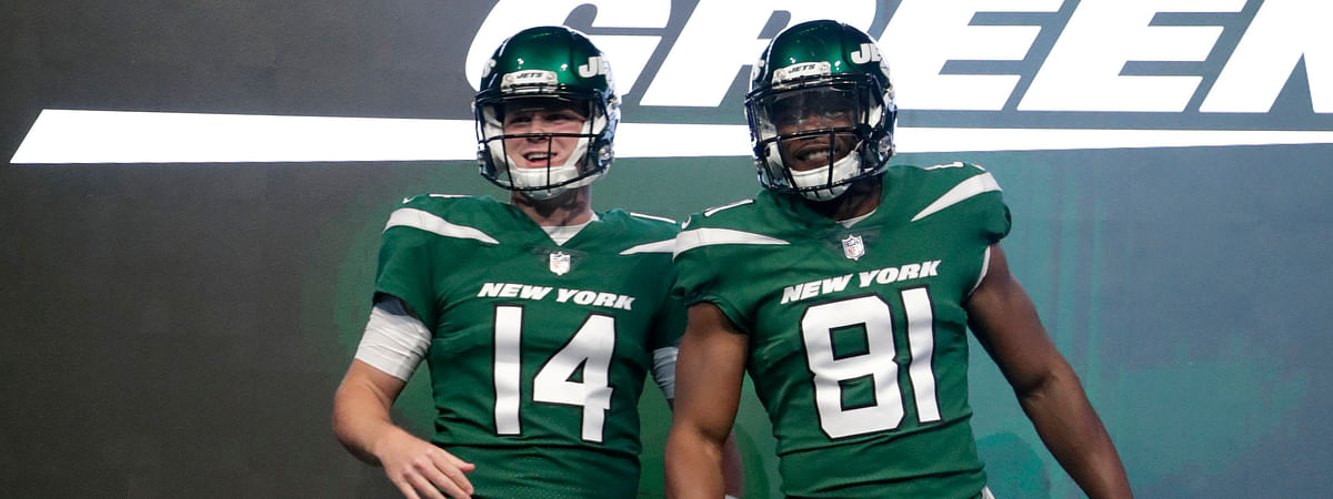 """New York Jets quarterback Sam Darnold (14) and wide receiver Quincy Enunwa (81) model the NFL football team's new """"Gotham green"""" uniforms on April 4, 2019."""