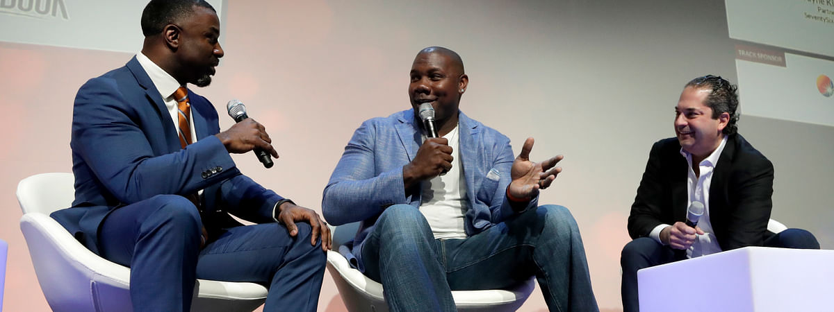 Former Philadelphia Eagles NFL football running back Brian Westbrook, left, talks with former Philadelphia Phillies baseball first baseman Ryan Howard, center, and Wayne Kimmel, partner at SeventySix Capital, during a panel talking about the move from professional athlete to entrepreneur at the Betting On Sports America conference on April 24, 2019.