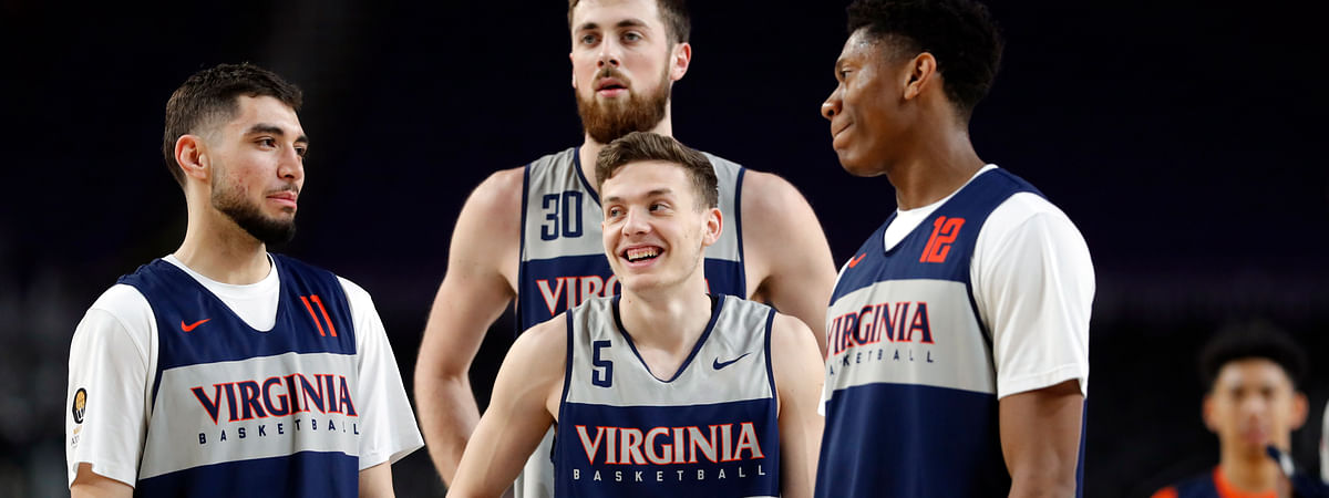 Virginia's Kyle Guy (5) laughs as he gather with Ty Jerome (11), Jay Huff (30) and De'Andre Hunter (12) during a practice session at the Final Four, Friday, April 5, 2019, in Minneapolis. (AP Photo/Charlie Neibergall)