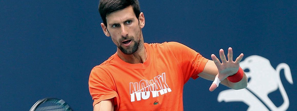In this March 18, 2019, file photo, Novak Djokovic hits during a practice round for the Miami Open tennis tournament at Hard Rock Stadium in Miami Gardens, Fla.